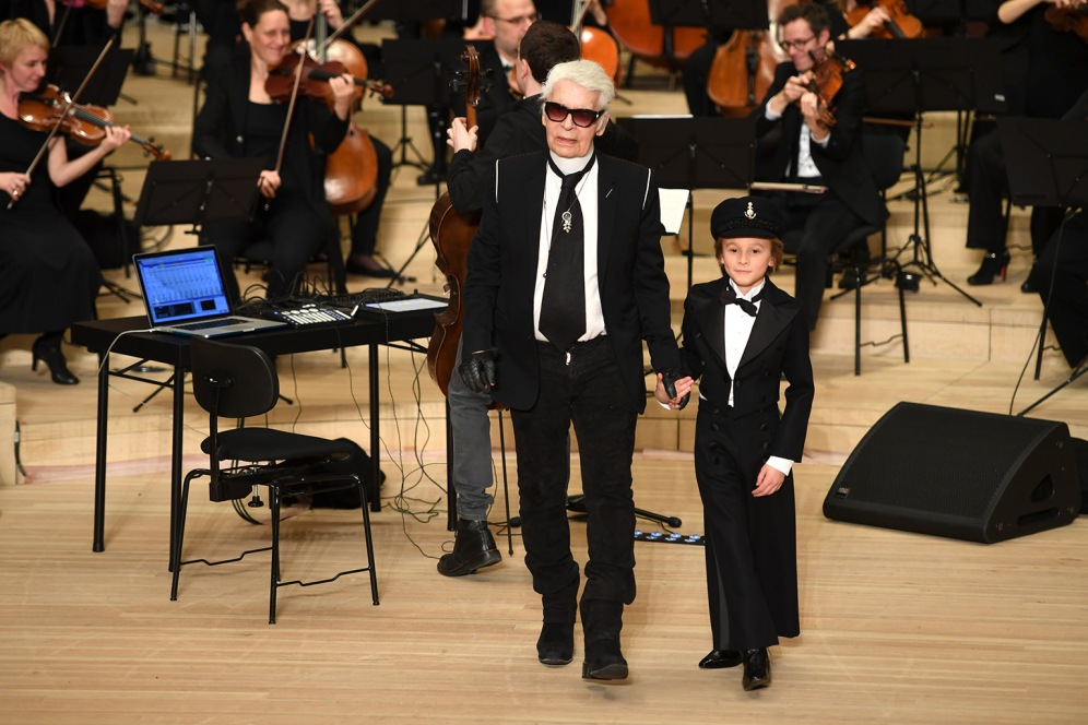 """German fashion designer Karl Lagerfeld and his godson Hudson Kroenig walk on stage after models presented creations for Chanel during the """"Chanel defilee"""" fashion show at the Elbphilarmonie in Hamburg, nothern Germany, on December 6, 2017. / AFP PHOTO / PATRIK STOLLARZ"""